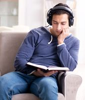 Young man reading book and listening to audio book