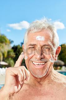 Senior Mann schützt Gesicht mit Sonnencreme