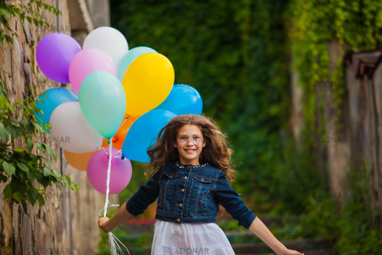 Girl is running with colorful balloons outdoors