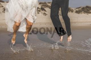 Couple of heterosexual couple having fun splashing waves on the beach.
