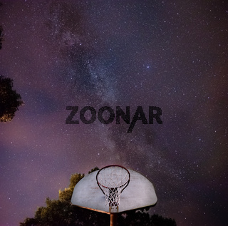basketball hoop at the park in the night with the stars above
