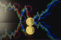 Bitcoins and virtual money concept. Gold bitcoins with chart of growing and falling valuance of a cryptocurrency. Mining or blockchain technology. Mining of bitcoins online bussiness. Trading.