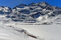 Rhätischen Bahn mit dem Bernina Express in der winterlichen Alpenlandschaft am Berninapass