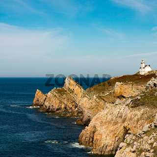 jagged rocky coastline with deep blue ocean and a white lighthouse