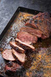 Barbecue dry aged wagyu tri tip steak with grill rub for smocking as closeup on a black metal sheet