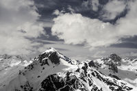 Black and white view on snowy sunlit mountains in clouds