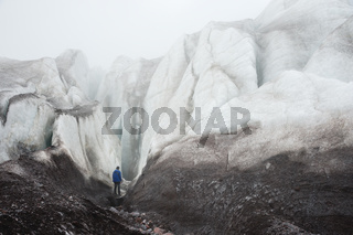 A free climber with an ice ax in his hand stands at the foot of the Great Glacier next to an epic crack in the fog in the mountains. Insurmountable obstacle
