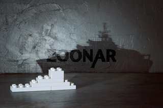 Plastic building blocks with ship shadow . Creative and ideal concept . Concrete interior background .