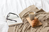 coffee, croissant, blanket and book on bed at home