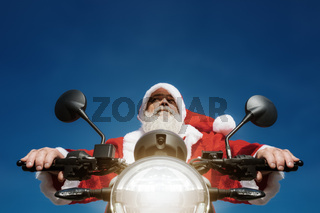 man on a motorbike in a typical Santa Claus costume