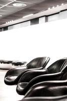 Schwarze Ledersessel in hellem Wartebereich mit weißer Wand