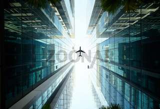 airplane flying above glass office buildings.