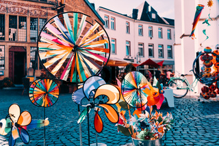 Colorful whirligigs contrasting with the background of a shopping street in Xanten