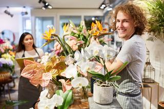 Junger Florist mit Sortiment an bunten Blumen