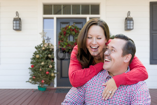 Happy Young Couple Laughing On Front Porch of House With Christmas Decorations