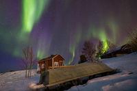 Polarlichter über einer Huette mit Boot im Schnee in Inari, Finland