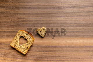Bread with heart-shaped cut and heart from bread. Wooden texture background.