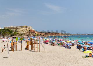 People enjoy summer holidays on the sandy beach Campoamor, Province Alicante, Spain