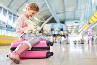 Kleines Mädchen im Flughafen spielt mit Plüschtier
