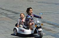 6 bis 8jähriges Mädchen fährt mit ihrem Bruder auf einem elektrisch betriebenen Motorrad, Mongolei