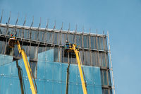 cranes on glass facade office building under construction -