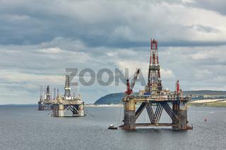 Large offshore oil rig drilling platforms off the coastline near Invergordon in Scotland.