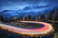 Blurred car headlights on winding road in mountains at night