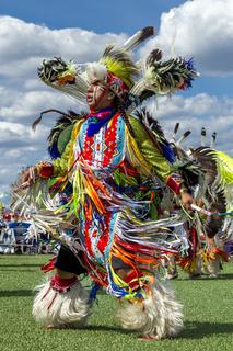 Native American man dancing at powwow.