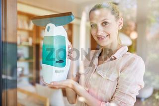Putzfrau mit elektrischem Fensterreiniger