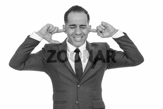 Mature handsome Persian businessman covering his ears