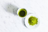 A cup of green matcha tea with matcha powder tea isolated on a light background.
