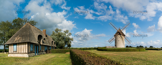 view of the historic windmill Moulin de Pierre and miller's house in Hauville in Normandy