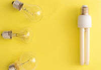 Energy-saving lamp vs. incandescent lamps on yellow background..Energy saving concept.