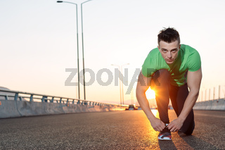 Urban jogger tying his running shoes on a big bridge. sunset highway