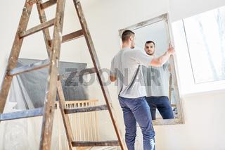 Mann beim Aufhängen von Spiegel in der Wohnung