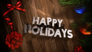 Closeup Happy Holidays text, gift boxes and green tree branches with balls on wood background