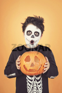 Happy Halloween.funny child in a skeleton costume with halloween pumpkin over on his head