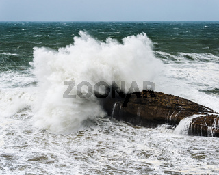Wave crashing on rock by a stormy day
