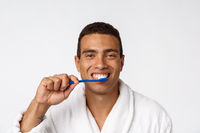 Man with tooth brush. African man holding a toothbrush with tooth brush and smiling while standing over white background.