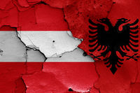 flags of Austria and Albania painted on cracked wall
