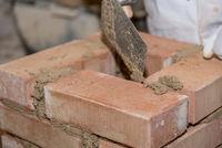 Handwerker errichtet Ziegelsteinwand mit kleinen Ziegelsteinen - Nahaufnahme Maurer