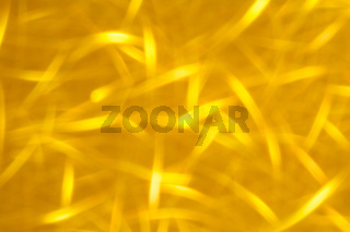 Abstract glitter golden glowing sparkling shiny background. Holiday gold wrapping paper texture. Christmas holiday seasonal wallpaper decoration. Greeting and wedding invitation card design template