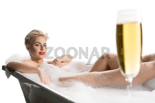 Beautiful model in bubble bath with glass of champagne