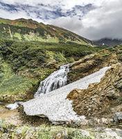 Mountain landscape of Kamchatka: beautiful waterfall. Summer landscape of Kamchatka