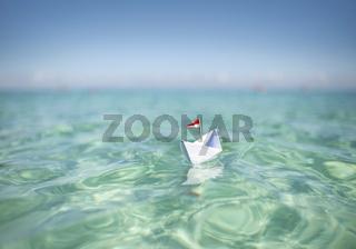 Papierschiff im türkisen Wasser | Urlaub & Reisen