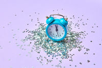 Blue vintage alarm clock on a lavender background with silver glitter.