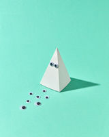 White plastic pyramid with eyes as Halloween simbol.