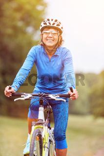 Ältere Frau beim Fahrrad fahren mit Mountainbike