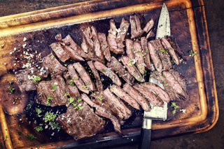 Traditional barbecue skirt steak sliced as close-up on a wooden board