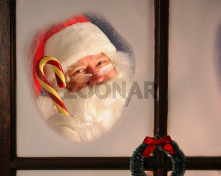 Santa Claus seen through a frosted window holding a large candy cane. Horizontal format.